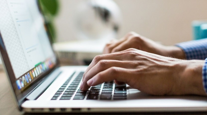 close-up of hands typing on a laptop